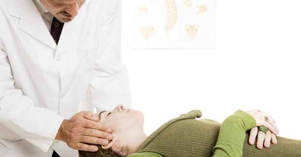 Chiropractor gently adjusting a patient's neck in his office.